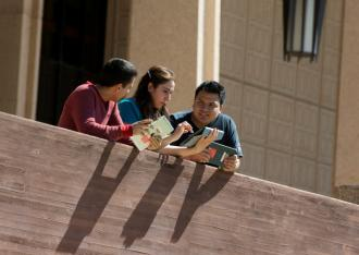 Students use iPads in front of library